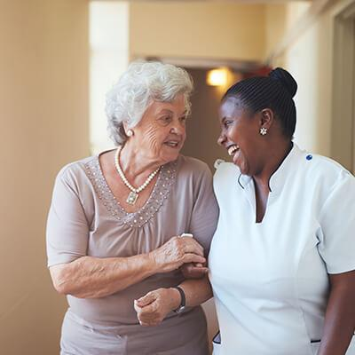 a caregiver talking to a senior woman suffering from presbycusis