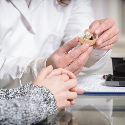Person holding hearing aid answering questions about hearing aids