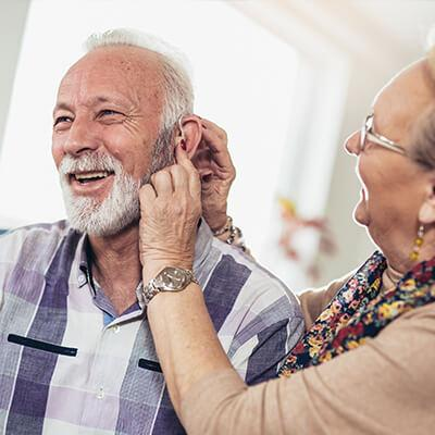 loved one having trouble with hearing assisted by wife