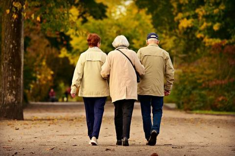 Elderly Woman Maintaining Balance by Holding Onto her Elderly Female and Male Friends' Arms