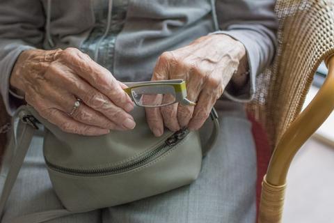 Elderly Woman's Hands Holding Glasses