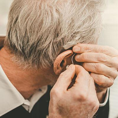 elderly man getting used to hearing aids